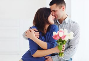 husband gives wife bouquet of flowers