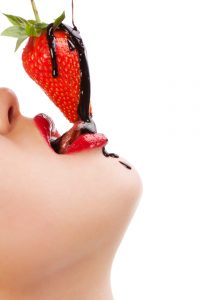woman seductively lick chocolate dipped strawberry