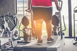 obese man running on curved treadmill in gym