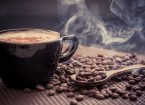 steaming cup of coffee and beans