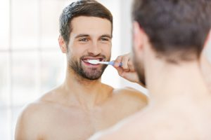 man brushing his teeth and happy with Progentra supplement