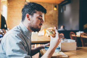 man enjoying a good burger