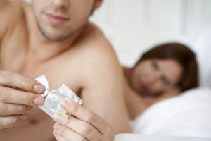 opening condom in bed